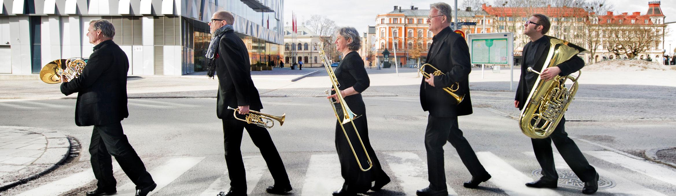Linnékvintetten gåendes över övergångsställe med sina instrument i händerna.