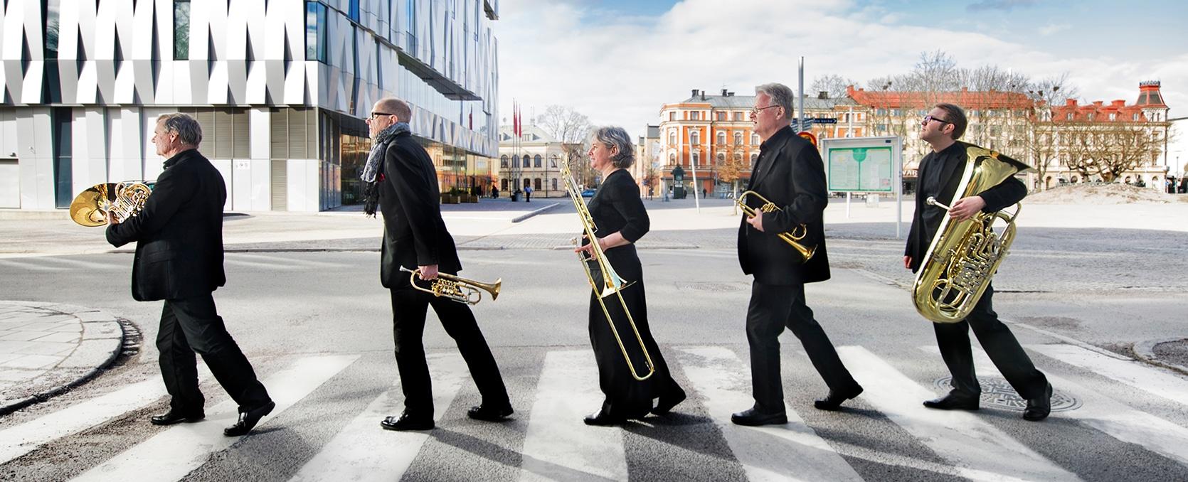 Linnékvintetten går över övergångsställe med sina instrument