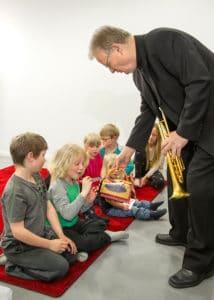 Barn som sitter på golvet och musikern Bengt Fagerström